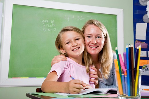 Stock Photo: 4172R-2787 Teacher and young student in class writing