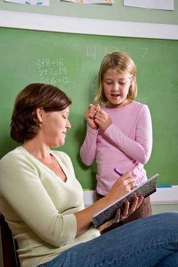 School girl and teacher by blackboard in classroom : Stock Photo