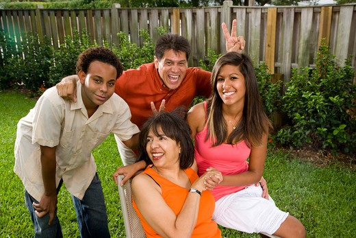 Interracial family relaxing in back yard : Stock Photo