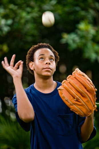 Teenage boy tossing a baseball up in the air : Stock Photo