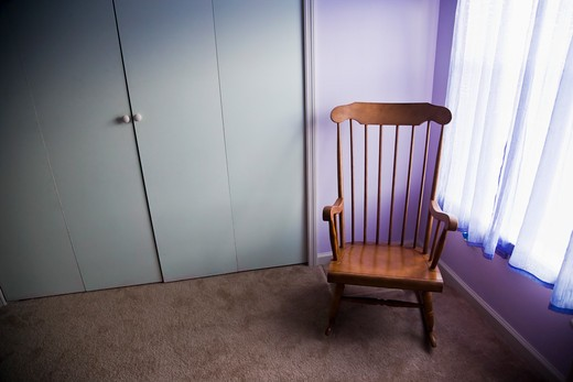 Empty rocking chair in room next to window : Stock Photo