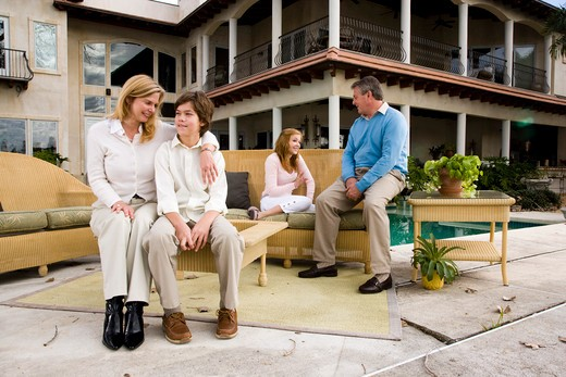 Family relaxing on patio together : Stock Photo