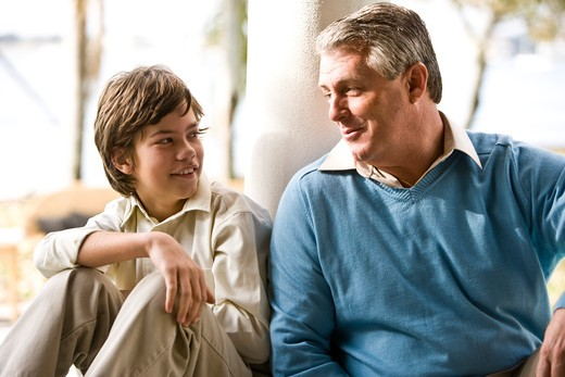 Stock Photo: 4172R-634 Father and son relaxing and conversing outdoors