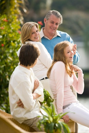 Mature couple dancing outdoors, daughter and son in foreground : Stock Photo