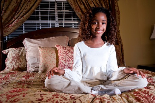 Cute 10 year old African American girl sitting on bed : Stock Photo