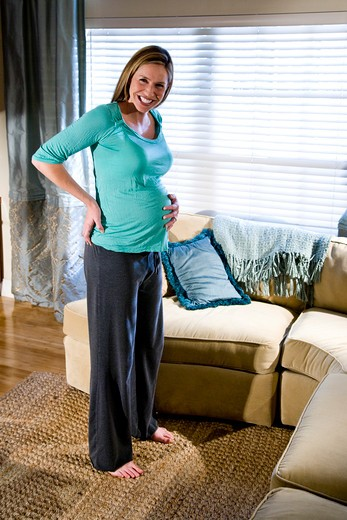 Stock Photo: 4172R-714 Happy pregnant woman standing in living room