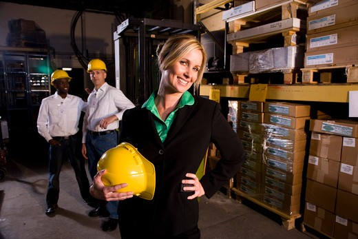 Workers with female boss in storage warehouse : Stock Photo