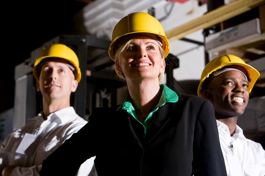 Office workers in storage warehouse wearing hard hats : Stock Photo