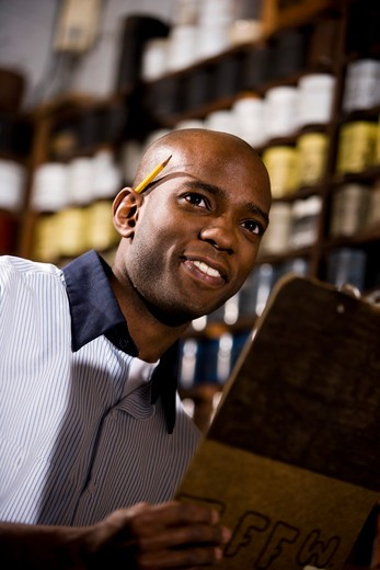 Young African American male worker working in print shop by shelves of ink : Stock Photo
