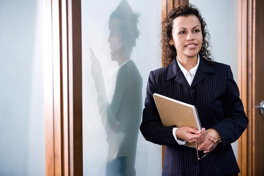 Stock Photo: 4172R-961 Confident Hispanic businesswoman in boardroom, colleague outside