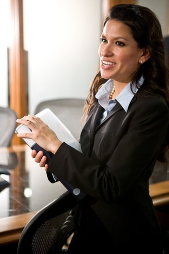 Confident young Hispanic businesswoman in boardroom : Stock Photo