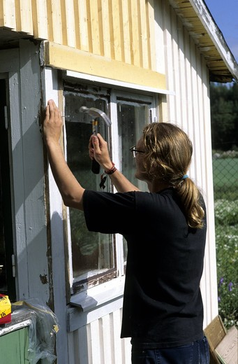 Young man with hammer renovating a house in Sweden : Stock Photo
