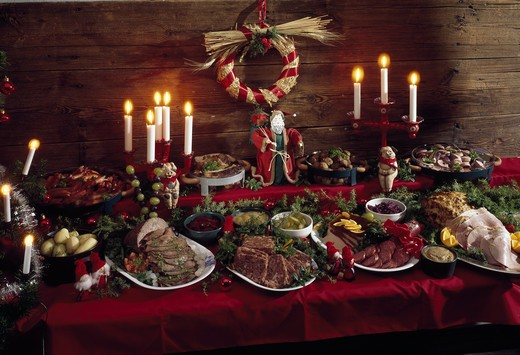 Stock Photo: 4176-11024 Dining table with christmasfood and lit candles