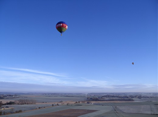 Hot air balloons soaring above fields : Stock Photo