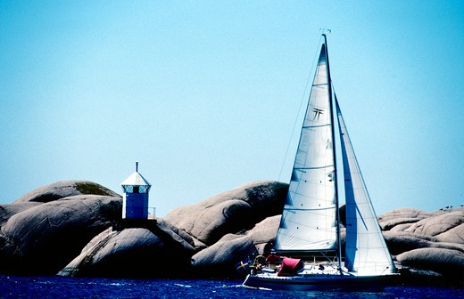 Sailboat sailing in the sea with rocks in the background : Stock Photo