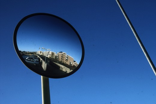 Reflection of a cars parked on a roadside in a round mirror : Stock Photo