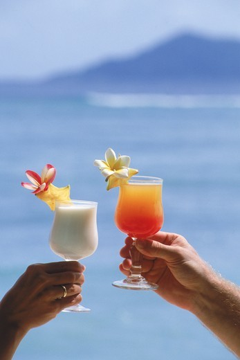 Couple on island holiday toasting with tropical drinks : Stock Photo