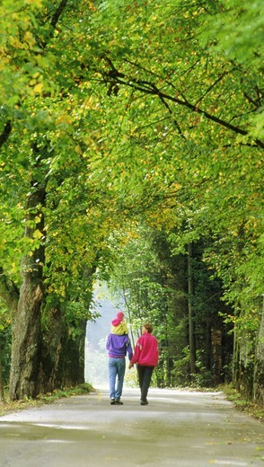 Family of three on tree-lined country road in Bavaria  Germany : Stock Photo