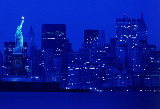 NIGHT TIME SKYLINE OF NEW YORK CITY AND STATUE OF LIBERTY : Stock Photo