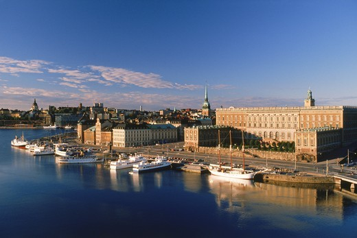 Boats anchored along Skeppsbron at sunrise with Royal Palace and Old Town in Stockholm : Stock Photo