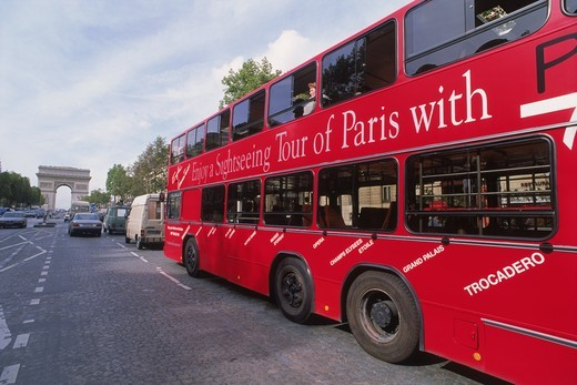 Red tour bus on Champs Elysees with Arc de Triomphe : Stock Photo