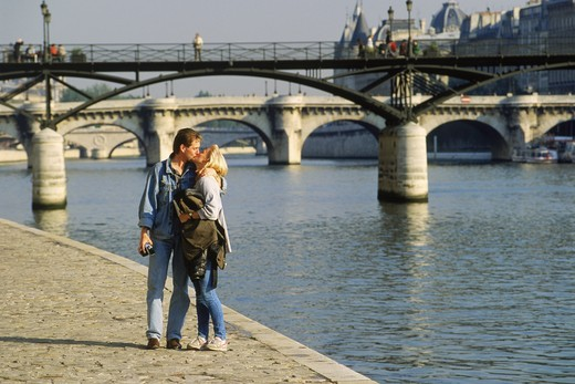Couple walking along River Seine near Pont des Arts in Paris : Stock Photo