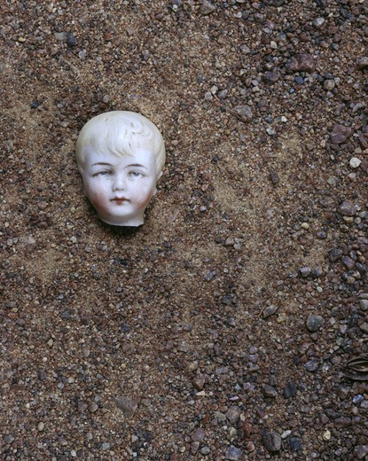 A head of a doll lying on the ground : Stock Photo