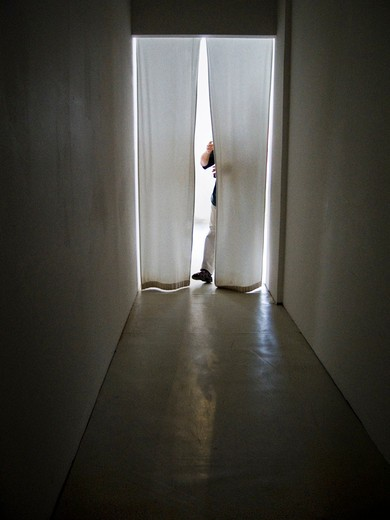 Stock Photo: 4176-16058 A person behind curtains in the doorway