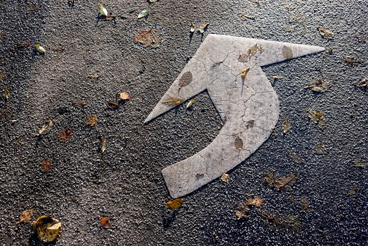 Close-up of a painted white arrow sign on a road : Stock Photo