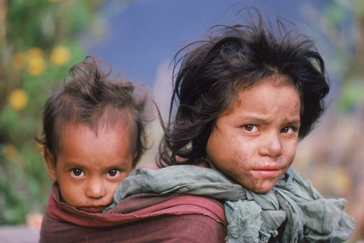 Girl carrying her baby brother or sister in back sling at Himalayan village in Nepal : Stock Photo