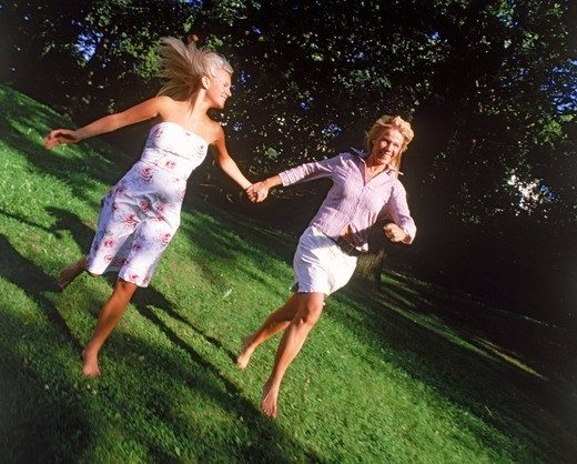 Stock Photo: 4176-20923 Mother and daughter running barefoot hand in hand on grass