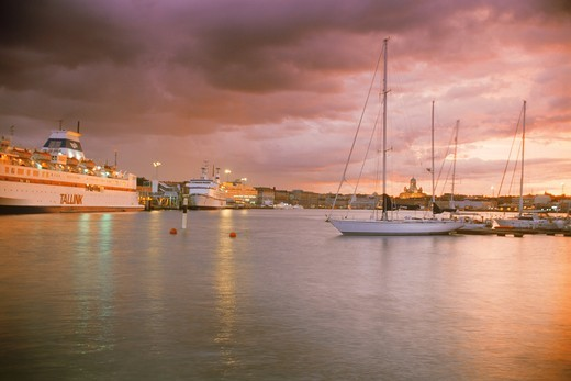 Stock Photo: 4176-20956 The Yacht Club on right and passenger ferries on left at South Harbor under sunset skies in Helsinki