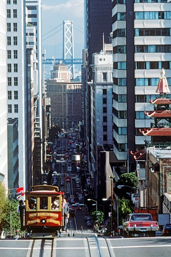 Cable car riding up California Street in downtown San Francisco with Oakland Bay Bridge : Stock Photo