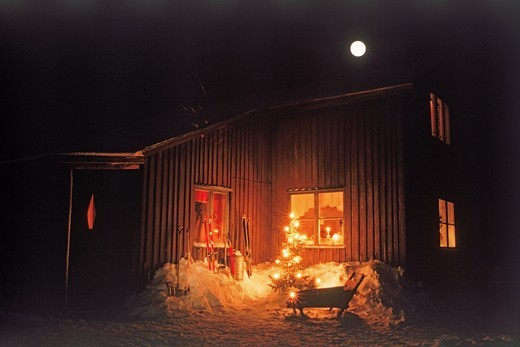 Stock Photo: 4176-21131 Home in Swedish Lappland above Arctic Circle with skiis, sled, shovel and Christmas tree under cold full moon
