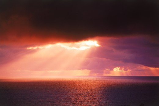 Stock Photo: 4176-21231 Sun rays bursting through cloudy skies over boundless ocean