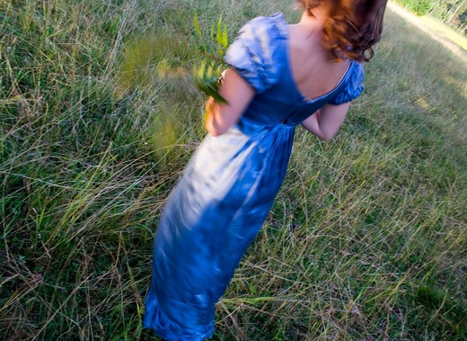 Rear view of a young woman walking in a lawn, Sweden : Stock Photo