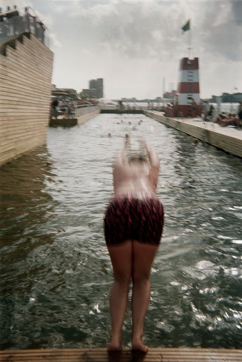 A girl jumping into a harbor-pool : Stock Photo