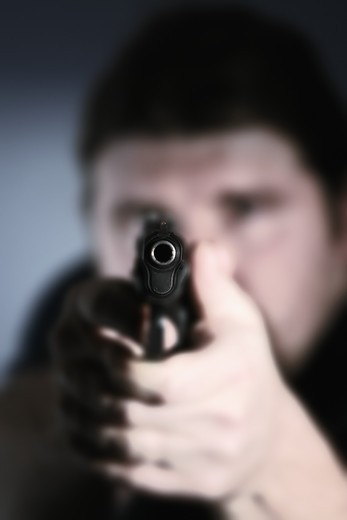 Close-up of a mid adult man aiming with a handgun : Stock Photo