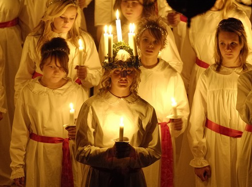 Group of girls standing and holding burning candles on Lucia Day : Stock Photo
