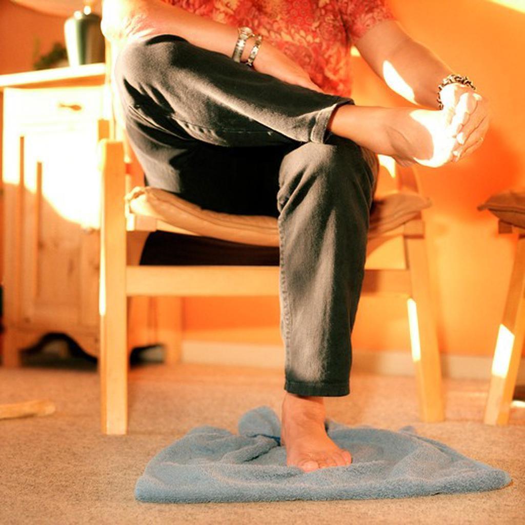 Woman massaging her feet : Stock Photo