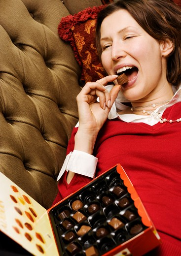 Close-up of a woman lying on a couch eating chocolate : Stock Photo