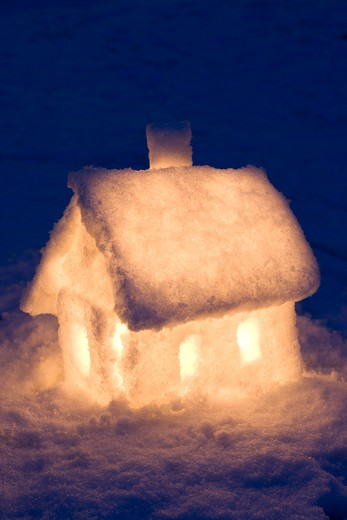 Little hut built in snow with candles in it : Stock Photo