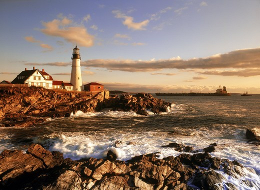 Ship passing Portland Head Lighthouse on coast of Maine at sunrise : Stock Photo