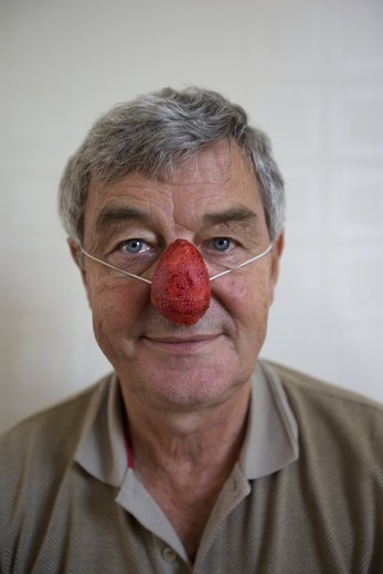 Stock Photo: 4176-27881 Portrait of a senior man wearing a clown's nose