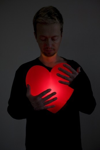 Heart shape lamp lit up in front of a man, Kalmar, Sweden. : Stock Photo