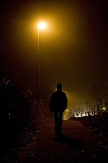 A dark night illuminated by streetlight. A person out walking, Kalmar, Sweden. : Stock Photo