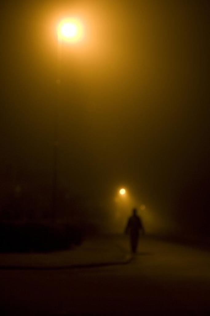 Stock Photo: 4176-28435 A night lit by streetlight. A person outside walking, Kalmar, Sweden.