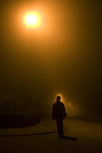 A night lit by streetlight. A person outside walking, Kalmar, Sweden. : Stock Photo