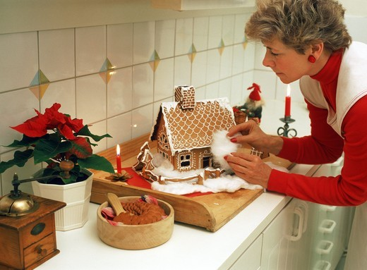 Mother baking and decorating Christmas gingerbread house in Swedish kitchen : Stock Photo