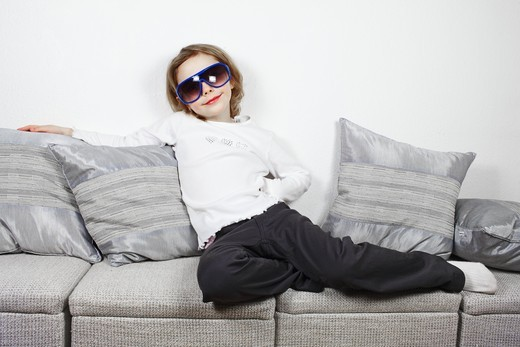 A young girl posing indoors with a pair of large sunglasses. : Stock Photo